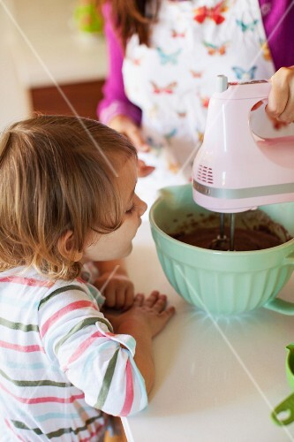 A small child watching her mother mixing batter