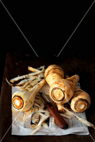 Several parsnips, partly peeled, on newspaper