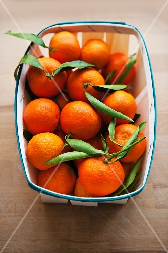 Fresh clementines with leaves in a woodchip basket