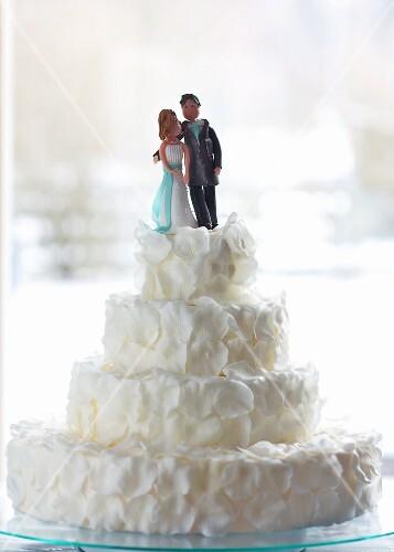 Originelle Hochzeitstorte geschmückt mit weissen Rosenblättern und ...