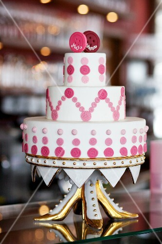 An unconventional wedding cake decorated with pink buttons on a gilded cake stand