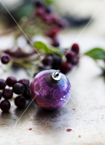 A purple Christmas bauble next to a sprig of aronia berries