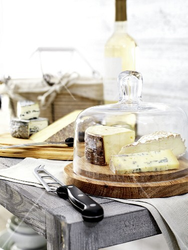 Assorted types of cheese under a cheese dome, and a cheese knife
