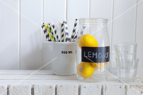 A jar of lemons, drinking straws and water glasses