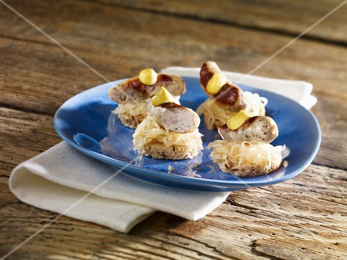 ... canapés of sauerkraut, grilled bratwurst and mustard – StockFood