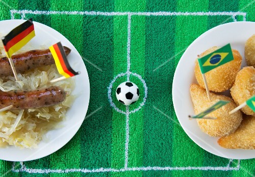 Sausages with cabbage (Germany) and salgadinhos (Brazil) with football-themed decoration