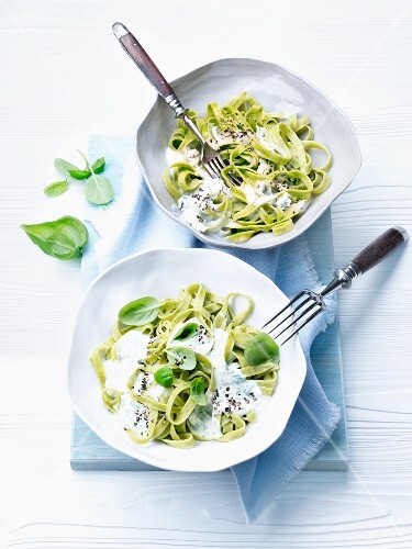 Green ribbon pasta with cream sauce and basil