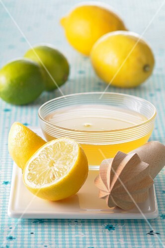 Lemon juice in a small dish, a lemon squeezer and citrus fruit