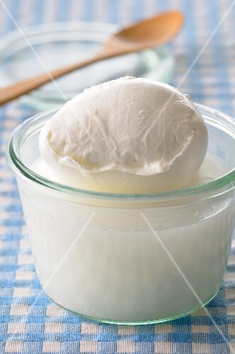 Mozzarella with brine in a glass pot