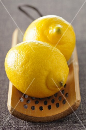 Two lemons on a wooden grater