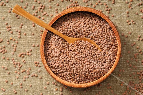 Lentils in a bowl with a wooden spoon