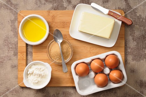 Assorted baking ingredients (eggs, sugar, butter, flour, olive oil)