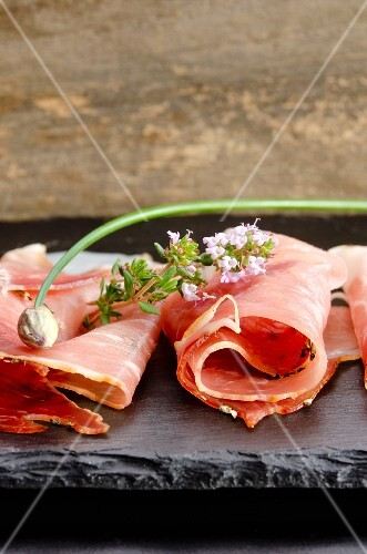 Black Forest ham with herbs on a slate slab