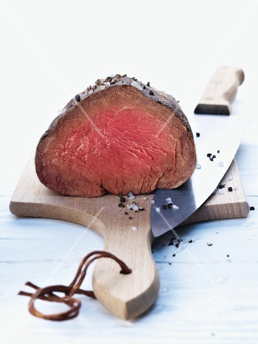 Fillet of beef with salt and black pepper on a chopping board