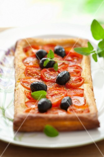 Puff pastry tart with cherry tomatoes, olives and oregano