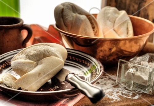 White French bread in a copper bowl and some on a plate
