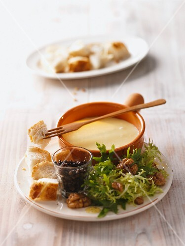 Cheese fondue with white bread and frisee salad with walnuts