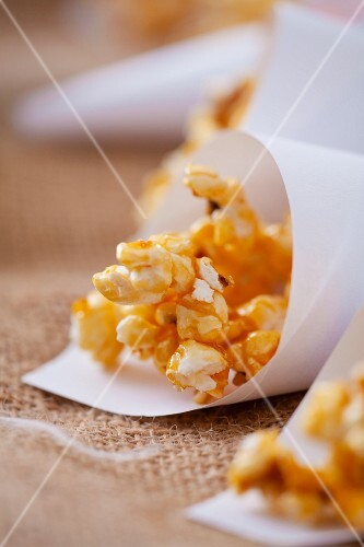 Caramelised popcorn in paper cones (close-up)