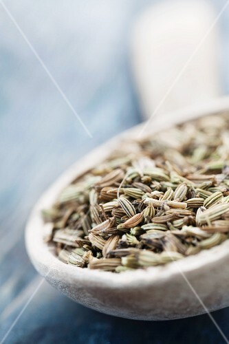 Dried fennel seeds in a deep wooden spoon on a blue background