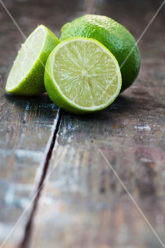Two lime halves and a whole lime on a wooden surface