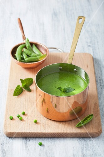 Cream of pea soup with mint in a copper saucepan