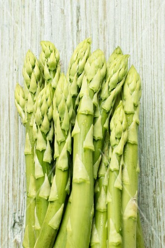 Green asparagus on wooden background