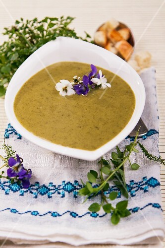 Herb soup with edible flowers