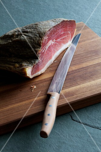 Raw ham with knife and board