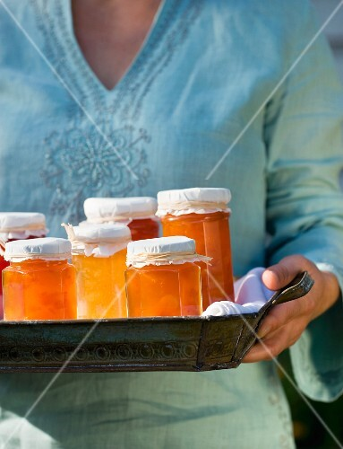 A woman holding a tray full of jars of jam