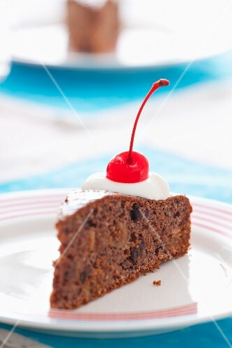 A slice of chocolate cake with dried fruit, cream and a glacé cherry