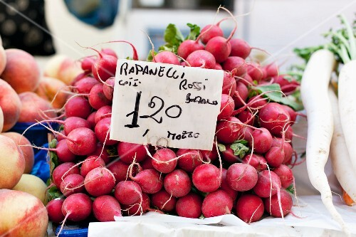 A pile of radishes at the market with a price sign