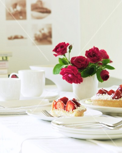 A table set with strawberry cake, a bunch of roses and a coffee set