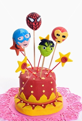 Cake pops decorated to look like superheroes, stuck into a cake