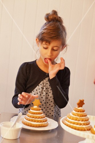 A girl decorating Christmas trees made from stacked Lebkuchen (spiced soft gingerbread from Germany)