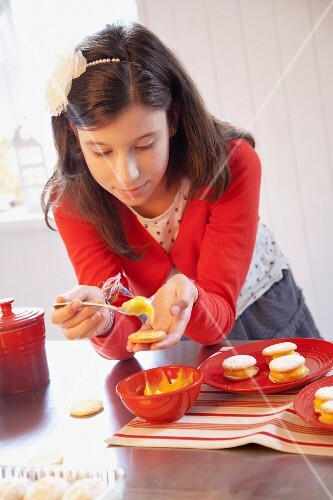 A girl filling biscuits with lemon curd