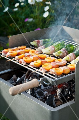 Romaine lettuce and apricots wrapped in bacon on the barbecue