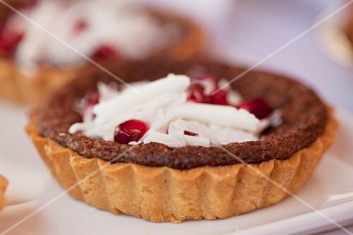 Individual chocolate tortes with grated chocolate and pomegranate seeds