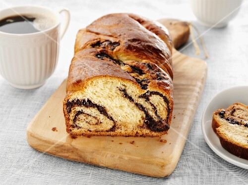 Chocolate Babka loaf on cutting board with slice and cup coffee.