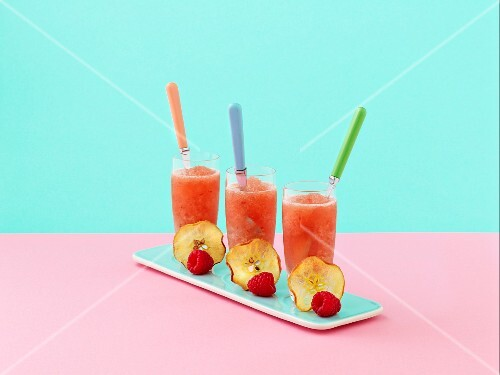 Three glasses of pink lady apple frappe, decorated with a slice of apple and a raspberry