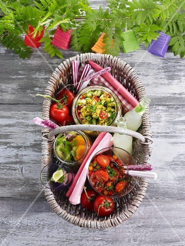 Assorted salads in a picnic basket on a wooden table