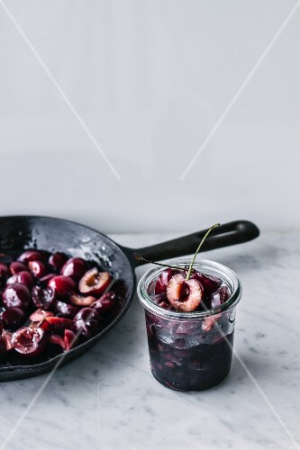 Fried cherries in a pan and in a storage jar