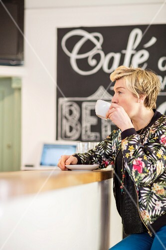 A woman sitting at the counter in a café, drinking coffee