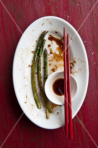 Remains of a meal of fried asparagus and soy sauce on a plate with chopsticks