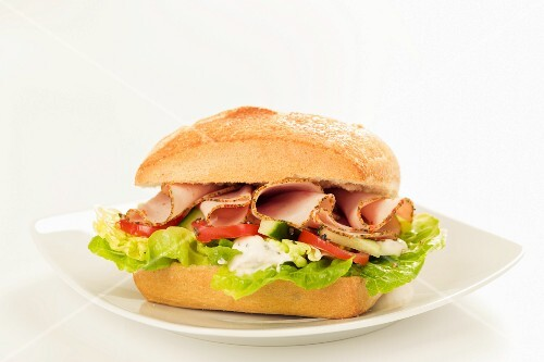 A sandwich filled with lettuce, tomatoes and sliced turkey