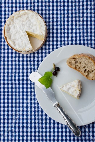 Camembert with a slice of baguette and blackcurrants (view from above)