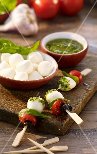 Skewers with mozzarella balls, tomatoes, basil, olives and pesto