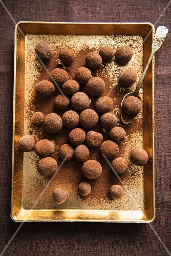 Chocolate truffles on a gold-coloured tray (view from above)