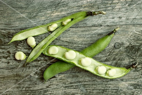 Broad beans in the pod on a wooden surface
