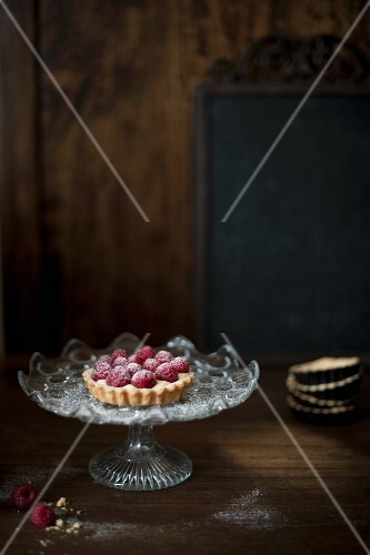 Small raspberry tart on a glass cake stand