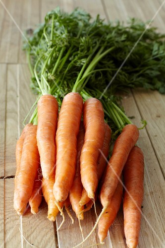 Fresh carrots on wooden planks